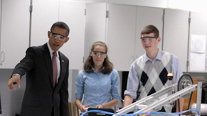 FILE - In this Sept. 16, 2011 file photo, President Barack Obama, with students Meghan Clark, center, and Nathan Hughes, right, watches as they demonstrate their FIRST Robot, during a visits to a classroom at Thomas Jefferson High School for Science and Technology in Alexandria, Va. America's decision to re-elect President Barack Obama over Republican presidential candidate, former Massachusetts Gov. Mitt Romney will impact key sectors of the American economy. During the President's first term, Obama signed into law the America Invents Act to streamline the U.S. patent process. The idea was that inventors and entrepreneurs could turn their ideas into products more quickly and create inexpensive ways to resolve disputes(AP Photo/Pablo Martinez Monsivais, File)