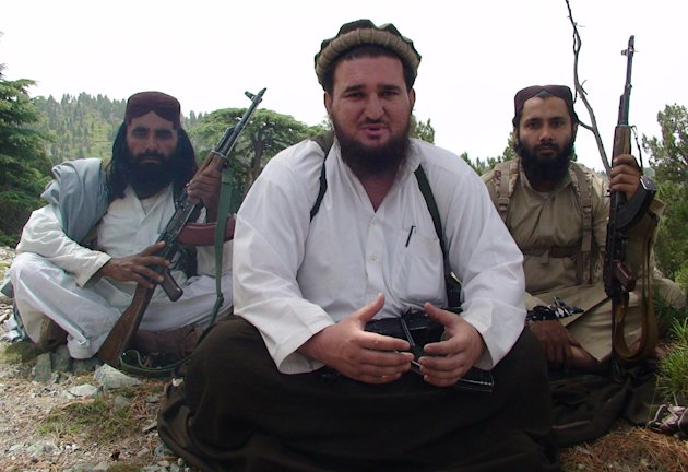 "In this photo taken Aug. 6, 2012 Pakistani Taliban spokesman Ahsanullah Ahsan, center, flanked by his body guards talks to The Associated Press in the militant group's stronghold of Shawal in Pakistani tribal region of South Waziristan. The Taliban have threatened to kill a Pakistani cricket star who has become a major political player if he holds a planned march to their tribal stronghold along the Afghan border to protest U.S. drone attacks. Ahsan said ""If he comes, our suicide bombers will target him,"" (AP Photo/ Ishtiaq Mahsud)"