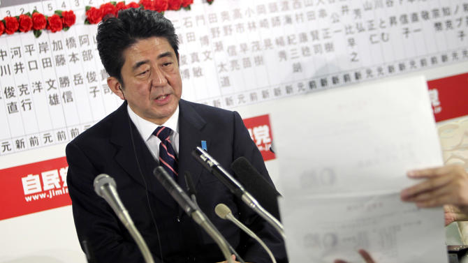 Japan's main opposition Liberal Democratic Party leader Shinzo Abe answers a reporter's question at the party headquarters in Tokyo, Sunday night, Dec. 16, 2012. The conservative LDP stormed back to power in parliamentary elections Sunday after three years in opposition, exit polls showed, signaling a rightward shift in the government that could further heighten tensions with rival China. (AP Photo/Junji Kurokawa)