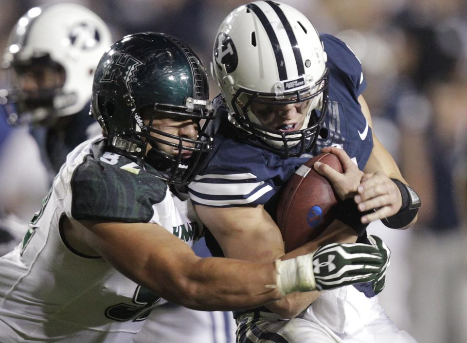Hawaii defensive lineman Beau Yap (92) tackles Brigham Young quarterback Taysom Hill during the third quarter of an NCAA college football game Friday, Sept. 28, 2012, in Provo, Utah. (AP Photo/Rick Bowmer)