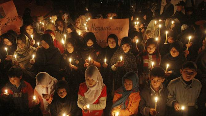 Pakistani children hold candles at the site of Saturday's bombing, in Quetta, Pakistan, Thursday, Feb. 21, 2013. Pakistani Shiites buried their kin killed in a massive bombing last weekend in the southwestern city of Quetta but the funeral on Wednesday was marred by gunfire as both protesters and police fired into the air. (AP Photo/Arshad Butt)