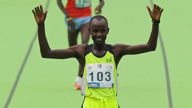 Julius Maisei of Kenya (front) celebrates after crossing the finish line to win the men's portion of the Hong Kong Marathon (AFP)