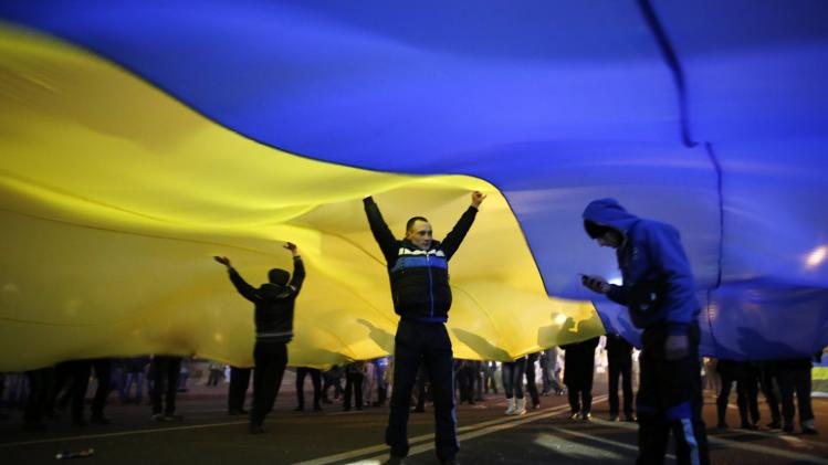 Pro-European integration protesters dance underneath a huge Ukrainian flag at Independence Square in Kiev