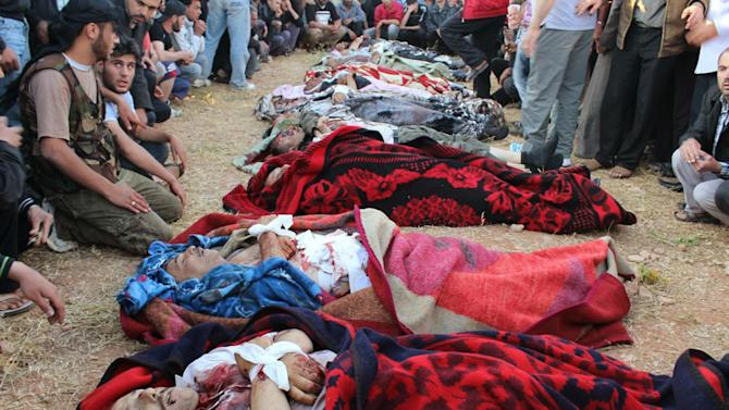 This Thursday, May 31, 2012 citizen journalism image provided by Shaam News Network SNN, purports to show Syrian mourners gathered around the bodies of eleven workers killed by gunmen on their way to work Thursday at a state-owned fertilizer factory in the central province of Homs, Syria. (AP Photo/Shaam News Network, SNN)  THE ASSOCIATED PRESS IS UNABLE TO INDEPENDENTLY VERIFY THE AUTHENTICITY, CONTENT, LOCATION OR DATE OF THIS HANDOUT PHOTO.