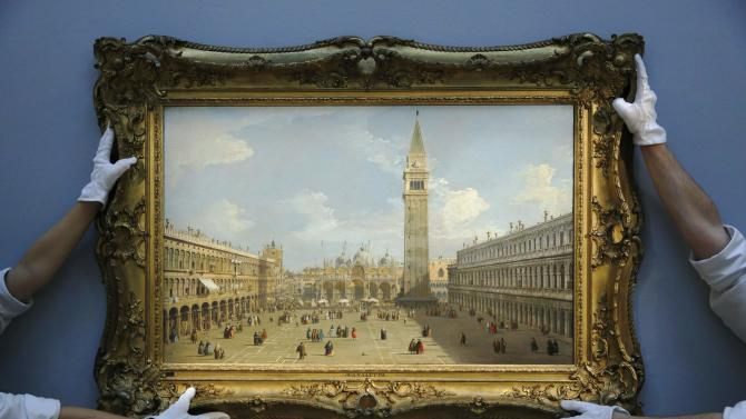 """Sotheby's employees pose with artist Canaletto's artwork """"Venice, The Piazza San Marco Looking East Towards The Basilica"""" at Sotheby's auction house in London"""