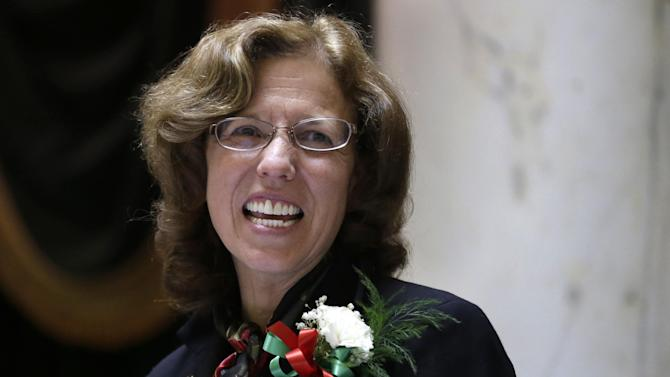 In this Tuesday, March 19, 2013 photo Rhode Island Senate President Teresa Paiva Weed smiles while at the rostrum in the Senate Chamber at the Statehouse, in Providence, R.I. Paiva Weed said she intends to vote against gay marriage legislation in the Rhode Island Senate Wednesday. (AP Photo/Steven Senne)