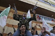 Syrian rebel fighters protest against the regime of Syrian President Bashar al-Assad in the northern city of Aleppo on October 12, 2012. The army took a pounding at the hands of rebels in northern Syria, a watchdog said, as tensions between Damascus and Ankara escalated over cargo seized from a Syrian passenger plane