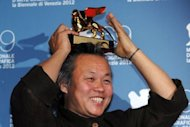 South Korean film director Kim Ki-Duk holds the Golden Lion for best movie following the award ceremony of the 69th Venice Film Festival
