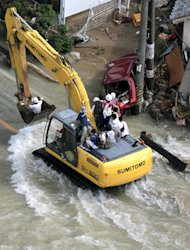 An excavator with evacuees makes its way through a flooded road after Typhoon Talas brought heavy rains at Nachi-Katsuura, central Japan, Monday, Sept. 5, 2011. The storm dumped record amounts of rain Sunday in western and central Japan as it turned towns into lakes, washed away cars and triggered mudslides that obliterated houses. (AP Photo/Kyodo News) JAPAN OUT, MANDATORY CREDIT, NO LICENSING IN CHINA, FRANCE, HONG KONG, JAPAN AND SOUTH KOREA