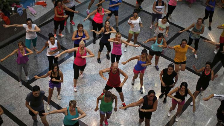 People take part in an aerobics class at a shopping centre in Malaga