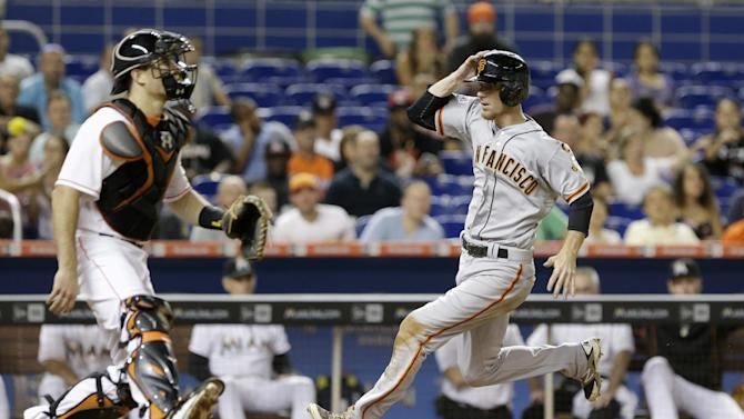 San Francisco Giants' Matt Duffy comes in to score on a sacrifice fly by Brandon Belt as Miami Marlins catcher J.T. Realmuto, left, waits for the throw during the sixth inning of a baseball game, Wednesday, July 1, 2015, in Miami. (AP Photo/Wilfredo Lee)