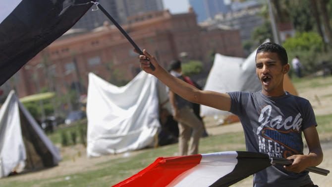 An Egyptian flag vendor waves flags in front of new erected strike tents in Tahrir Square, the focal point of Egyptian uprising in Cairo, Egypt, Saturday, June 22, 2013. Egypt's largest opposition grouping is reaching out to members of Hosni Mubarak's ruling party as it gears up for a protest campaign against the current Islamist president. (AP Photo/ Amr Nabil)