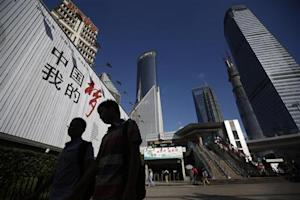 People walk past a billboard at the financial district of Pudong in Shanghai