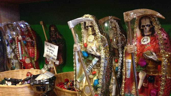 """FILE - In this Feb. 13, 2013 file photo, statues of La Santa Muerte are shown at the Masks y Mas art store in Albuquerque, N.M. As """"Breaking Bad"""" finishes filming its fifth and final season in Albuquerque, the popularity of the show is providing a boost to the economy and creating a dilemma for local tourism officials as they walk the fine line of profiting from a show that centers around drug trafficking, addiction and violence.  The store provided the statues used in the chilling opening scene of the show's third season, in which a pair of cartel assassins crawl to the saint's shrine in Mexico to request some divine help. (AP Photo/Russell Contreras, File)"""