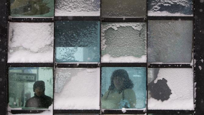 Riders wait in a bus stop where color-tinted windows collect snow during a storm, Friday, Feb. 8, 2013, in Portland, Maine. The National Weather Service says a blizzard warning is issued Friday evening for the southern coast. The forecast calls for up to 2 feet of snow and winds gusting to 50 mph.(AP Photo/Robert F. Bukaty)