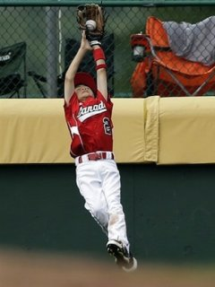 Canadian outfielder Carter Kada-Wong leaps for a miraculous catch — Associated Press