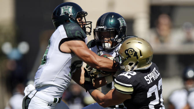 Hawaii defensive back Ne'Quan Phillips, center, intercepts pass intended for Colorado wide receiver Nelson Spruce, right, as Hawaii defensive back Michael Martin covers during the first quarter of an NCAA college football game in Boulder, Colo., Saturday, Sept. 20, 2014. (AP Photo/David Zalubowski)