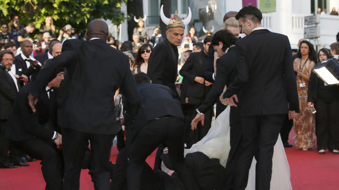 CORRECTS TO REMOVE REFERENCE TO DJIMON HOUNSOU AT LEFT Security run toward an unidentified man who ran unauthorized onto the red carpet during arrivals for the screening of How to Train Your Dragon 2 at the 67th international film festival, Cannes, southern France, Friday, May 16, 2014. (AP Photo/Alastair Grant)