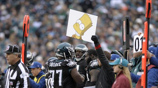 In this Dec. 1, 2013 file photo, Philadelphia Eagles sports science coordinator Shaun Huls holds a placard, center, during the second half of an NFL football game against the Arizona Cardinals, in Philadelphia. Eagles rookie head coach Chip Kelly finds signs better for communicating then microphones because the whole team can see the information and speed up his lightning-fast offense