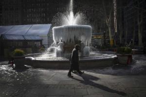 A man walks past the ice-covered Josephine Shaw Lowell Memorial Fountain, in frigid temperatures in Bryant Park in the Manhattan borough of New York City