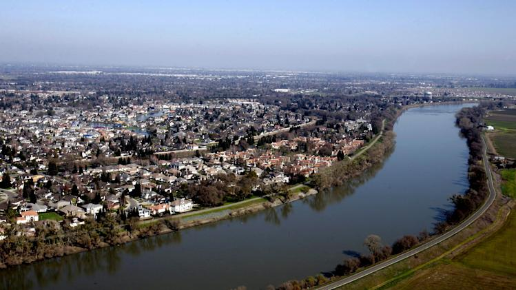 This Feb. 22, 2006 file photo shows houses located in the Pocket Area of Sacramento, Calif. along the Sacramento River. California water officials are set to release the revisions of the first four draft chapters of a $23 billion plan to restore and protect the Sacramento-San Joaquin Delta ecosystem and guarantee a stable water supply for millions of Californians. The Bay Delta Conservation Plan, known as the BDCP for short, is a federal and state initiative financed by California's water contractors, which includes recommendations for a twin tunnel project in the delta to carry water to vast farmlands and thirsty cities. (AP Photo/Rich Pedroncelli, File)
