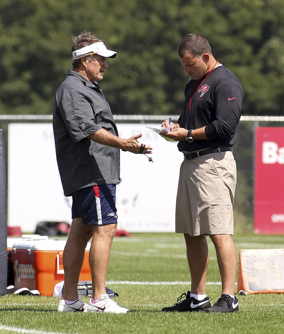 New Engladn Patriots coach Bill Belichick, left, talks with Tampa Bay Buccaneers coach Greg Schiano during a joint workout at NFL football training camp, in Foxborough, Mass., Thursday, Aug. 15, 2013. (AP Photo/Stew Milne)