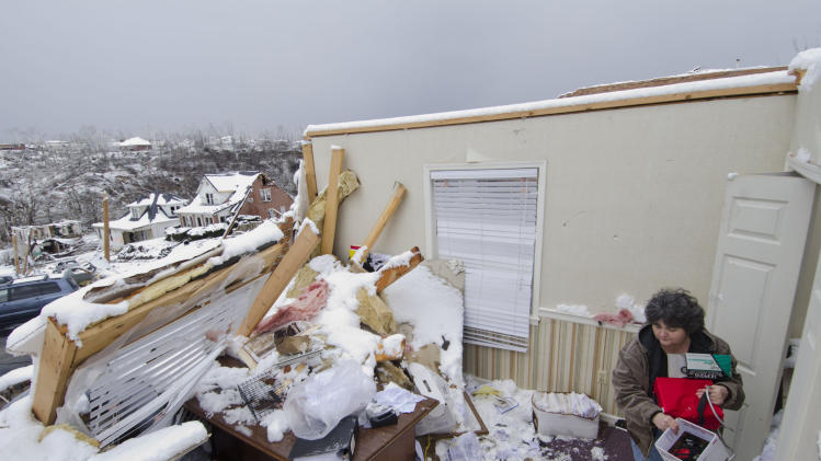 Rhonda Dixon clears out records and other items from the Morgan County Home Health Agency, Monday March 5, 2012 in West Liberty, Ky. The tornado that hit the town last Friday, tore off the roof and back walls to the clinic. (AP Photo/John Flavell)