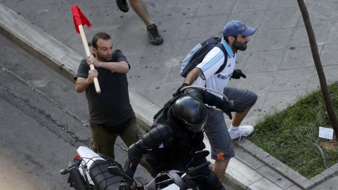 Anti-austerity demonstrators tussle with a motorcycle policeman in Syntagma Square in Athens during an anti-Austerity rally