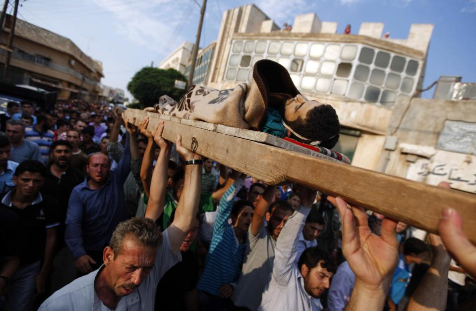 Syrian mourners carry the body of 29 year-old Free Syrian Army fighter, Husain Al-Ali, who was killed during clashes in Aleppo, during his funeral in the town of Marea on the outskirts of  Aleppo city, Syria, Thursday, Aug. 9, 2012. (AP Photo/ Khalil Hamra)