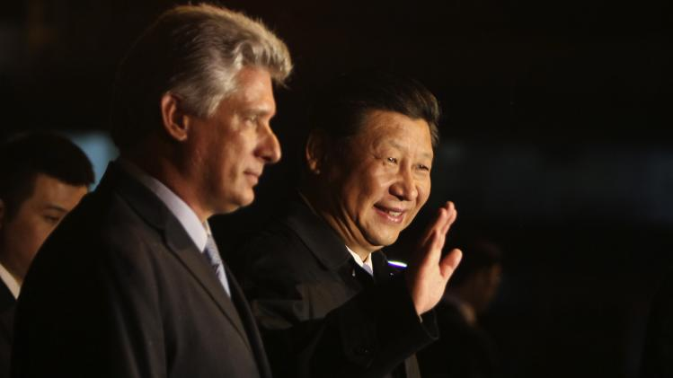 China's President Xi Jinping, center, waves to the press accompanied by Cuba's Vice President Miguel Diaz-Canel, left, at his arrival at the Jose Marti International Airport in Havana, Cuba, Monday, July 21, 2014. Xi Jinping is in Cuba for a two day official visit. (AP Photo/Ladyrene Perez, Cubadebate)