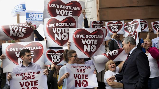 Two Yes campaign posters are held up at top left, beside a group of No campaign supporters holding up posters as former British Prime Minister and No campaigner for the Scottish independence referendum Gordon Brown, right, briefly speaks to them as he leaves after delivering a speech at a No campaign event in Glasgow, Scotland, Wednesday, Sept. 17, 2014.  Will the ayes have it, or will Scotland say naw thanks?  No one is certain. Excitement and anxiety mounted across the country Wednesday, the final day of campaigning before Thursday's referendum on independence.  With opinion polls suggesting the result is too close to call and turnout expected to reach record levels, supporters of separation feel they are within touching distance of victory — but wonder whether their surge in the polls will be enough.  (AP Photo/Matt Dunham)