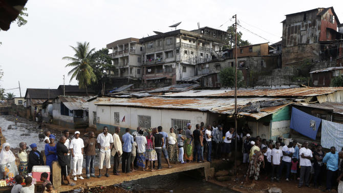 Voters wait in line to cast their ballots in presidential, parliamentary, and local elections, outside a polling station in the Kroo Bay neighborhood of Freetown, Sierra Leone, Saturday, Nov. 17, 2012. A decade after Sierra Leone's brutal civil war, voters on Saturday chose between an incumbent president who has provided new roads and free health care and a field of opposition candidates who decry the poverty and pace of economic recovery.(AP Photo/Rebecca Blackwell)
