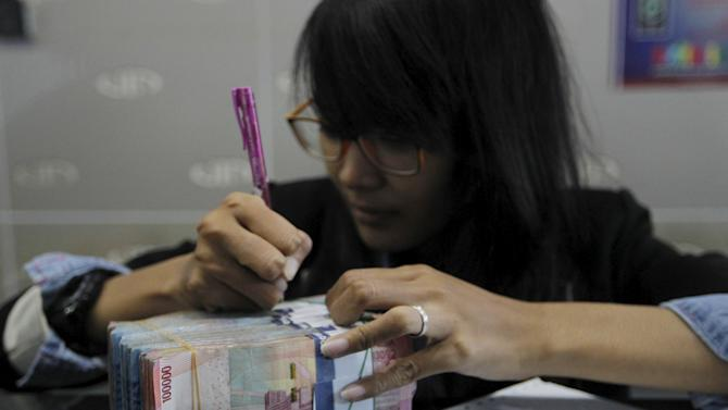 A money changer prepares Indonesian rupiah for a customer in Jakarta
