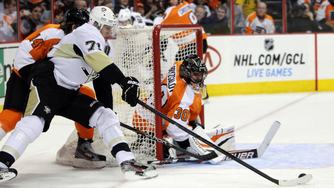Philadelphia Flyers goalie Ilya Bryzgalov defends the goal as Pittsburgh Penguins' Evgeni Malkin maneuvers the puck in the first period of an NHL hockey game, Thursday, March 7, 2013, in Philadelphia. (AP Photo/Tom Mihalek)