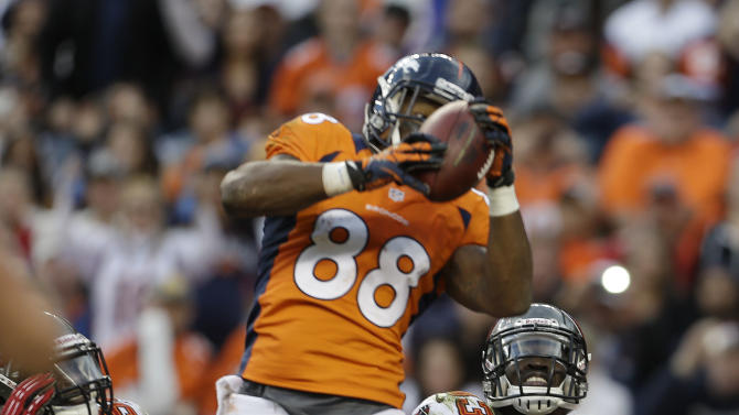 Denver Broncos wide receiver Demaryius Thomas (88) catches a pass for a touchdown as Tampa Bay Buccaneers free safety Ahmad Black (43) and outside linebacker Lavonte David (54) defend in the third quarter  of an NFL football game, Sunday, Dec. 2, 2012, in Denver. (AP Photo/Joe Mahoney)