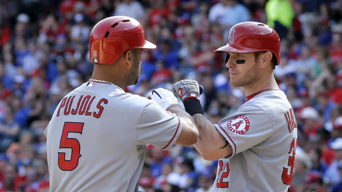 Los Angeles Angels' Albert Pujols (5) is congratulated by Josh Hamilton, right, after hitting a solo home run off in the sixth inning of a baseball game against the Texas Rangers, Saturday, April 6, 2013, in Arlington, Texas. Pujols homered twice to offset another tough day for Hamilton in his second game back in Texas, and the Angels beat the Rangers 8-4 Saturday. (AP Photo/Tony Gutierrez)