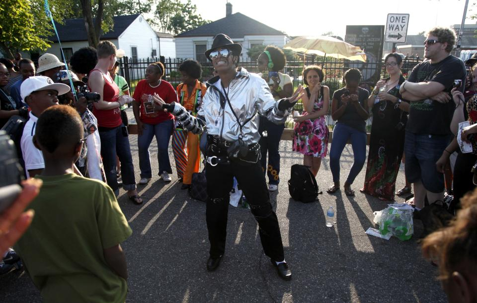 Michael Jackson impersonator Dominique Wilson performs to recorded music outside Jackson's boyhood home during celebrations marking what would have been Jackson's 54th birthday Wednesday, Aug. 29, 2012, in Gary, Ind.  (AP Photo/Charles Rex Arbogast)