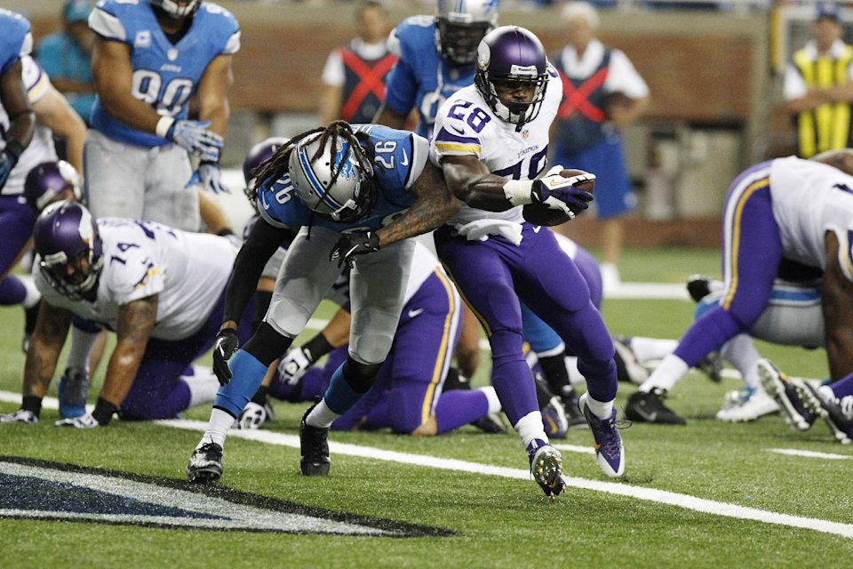 Minnesota Vikings running back Adrian Peterson (28), defended by Detroit Lions free safety Louis Delmas (26), runs into the end zone for a 4-yard touchdown during the second quarter of an NFL football game at Ford Field in Detroit, Sunday, Sept. 8, 2013