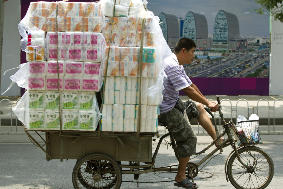 A tricycle porter transports packs of tissue paper outside a wholesale market in Beijing, China, Tuesday, July 10, 2012. China's June trade growth decelerated sharply as a slowdown in the world's second-largest economy deepened despite stimulus efforts. (AP Photo/Alexander F. Yuan)