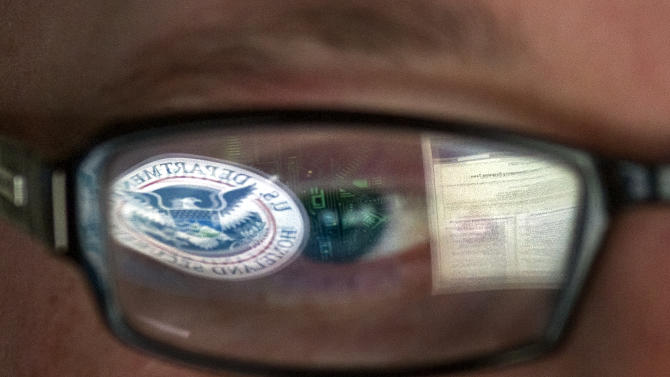 FILE - This Sept. 30, 2011 file photo shows a reflection of the Department of Homeland Security logo in the eyeglasses of a cybersecurity analyst at the watch and warning center of the Department of Homeland Security's secretive cyber defense facility in Idaho Falls, Idaho. The center is tasked with protecting the nation's power, water and chemical plants, electrical grid and other facilities from cyber attacks. (AP Photo/Mark J. Terrill, File)