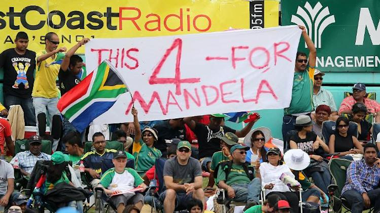 South Africa supporters hold a banner in memory of Nelson Mandela during the one-day international cricket match between India and South Africa in Durban on December 8, 2013
