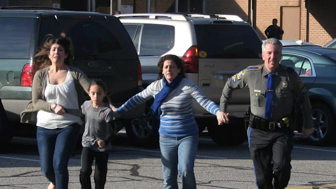 FILE - In this Dec. 14, 2012 file photo provided by the Newtown Bee, a police officer leads two women and a child from Sandy Hook Elementary School in Newtown, Conn., shortly after Adam Lanza opened fire, killing 26 people, including 20 children. While the people of Newtown do their best to cope with loss and preserve the memories of their loved ones, another class of residents is also finding it difficult to move on: the emergency responders who saw firsthand the terrible aftermath of last week's school shooting. (AP Photo/Newtown Bee, Shannon Hicks, File) MANDATORY CREDIT: NEWTOWN BEE, SHANNON HICKS