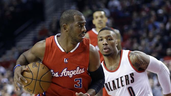 Los Angeles Clippers guard Chris Paul, left, drives past Portland Trail Blazers guard Damian Lillard during the first half of an NBA basketball game in Portland, Ore., Wednesday, April 1, 2015.  (AP Photo/Don Ryan)