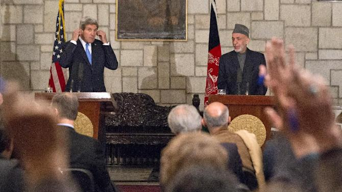 """Secretary of State John Kerry and Afghan President Hamid Karzai take questions during their joint newss conference at the Presidential Palace in Kabul, Monday, March 25, 2013. Kerry and Karzai made a show of unity Monday, shortly after the U.S. military ceded control of its last detention facility in Afghanistan, ending a longstanding irritant in relations between the two countries. Kerry, in Afghanistan for an unannounced visit, said he and Karzai were """"on the same page"""" when it comes to peace talks with the Taliban. (AP Photo/Jason Reed, Pool)"""