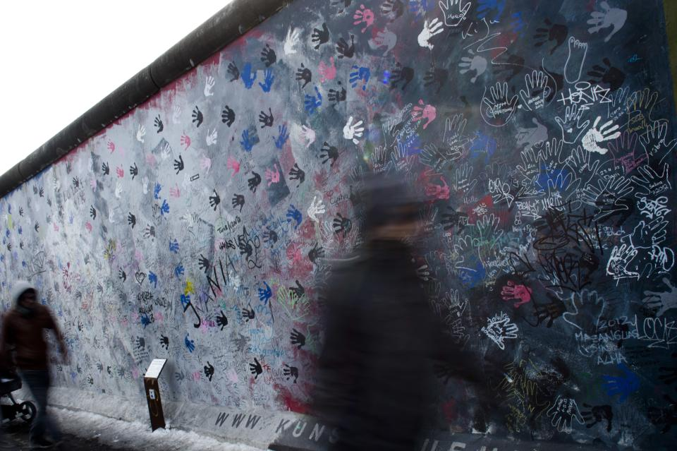 People walk in front of the East Side Gallery named part of the former Berlin Wall during a protest against the removal of a section of the historic part of the Wall, in Berlin, Sunday, March 17, 2013.  (AP Photo/Markus Schreiber)