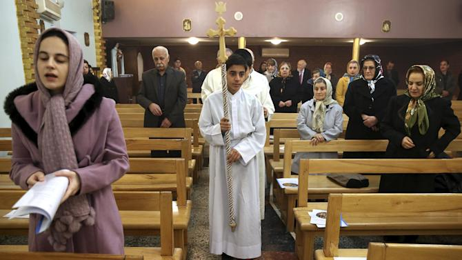 Iranian Christians attend Mass in Christmas Day at the Saint Mary Chaldean-Assyrian Catholic church in Tehran, Iran, Thursday, Dec. 25, 2014. Iran's minority group of Christians are celebrating Christmas and preparing for the new year. According to official figures, around 120,000 Christians live in Iran, mostly in central and northwestern parts of the country. Iranian Christians represent part of the parliament and freely practice their religion as allowed under the constitution. Other minorities, such as the Jews and Zoroastrians, are recognized in the same way by the law. (AP Photo/Ebrahim Noroozi)