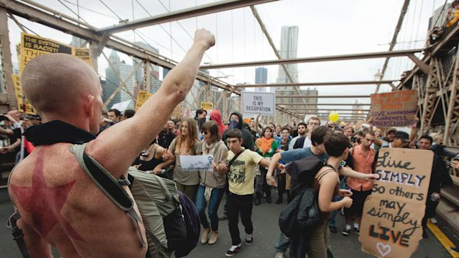 A large group of protesters affiliated with the Occupy Wall Street movement attempt to cross the Brooklyn Bridge, effectively shutting parts of it down, Saturday, Oct. 1, 2011 in New York. Police arrested dozens while trying to clear the road and reopen for traffic.(AP Photo/Will Stevens)