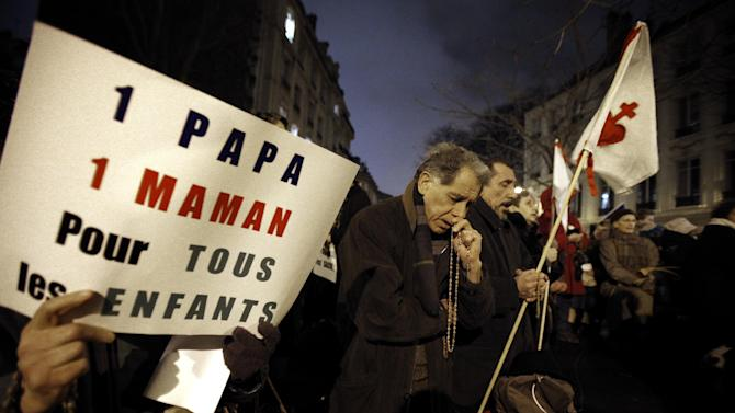 """Opponents to gay marriage pray during a demonstration in Paris, Tuesday, Jan. 29, 2013. The French government has presented a divisive plan to legalize gay marriage and adoption to Parliament for debate. The placard reads:  """"One Dad, One Mum for all the Children"""". (AP Photo/Christophe Ena)"""