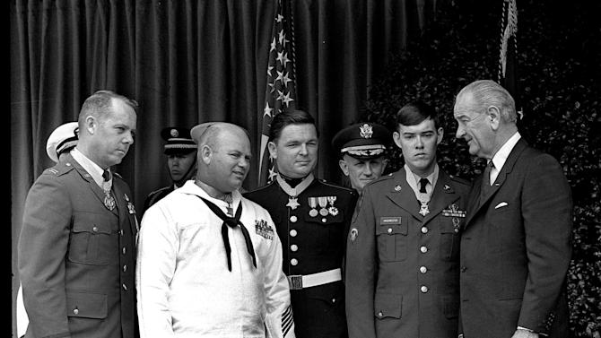 """FILE - In this May 14, 1968 file photo, U.S. President Lyndon Johnson, right, poses at the White House with four winners of the nation's highest award, the Medal of Honor. Decorated for valor in Vietnam, they are, from left: Air Force Capt. Gerald O. Young, of Anacortes, Wash.; Navy Bosn""""s Mate James E. Williams, of Rock Hill, S.C.; Marine Sgt. Richard A. Pittman, of Stockton, Calif., and Army Spc. 5  Charles C. Hagmeister, of Lincoln, Neb.  Others are unidentified. Pittman and the other recipients can proudly and truthfully say they were awarded the Medal of Honor for their valor in Vietnam. After a recent Supreme Court ruling, anyone else is free under the First Amendment to make the same claim, whether it's true or not. (AP Photo/File)"""