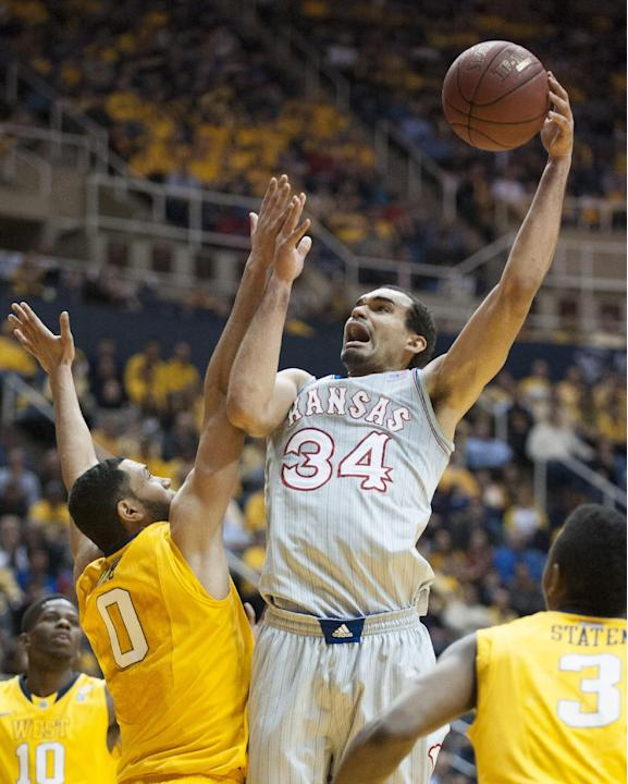Kansas' Perry Ellis, right, shoots over West Virginia's Remi Dibo during the first half of an NCAA college basketball game Saturday, March 8, 2014, in Morgantown, W.Va
